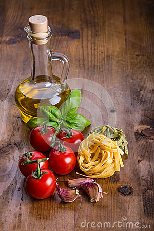Free Italian And Mediterranean Food Ingredients On Wooden Background.Cherry Tomatoes Pasta, Basil Leaves And Carafe With Olive Oil. Royalty Free Stock Photography - 55605547