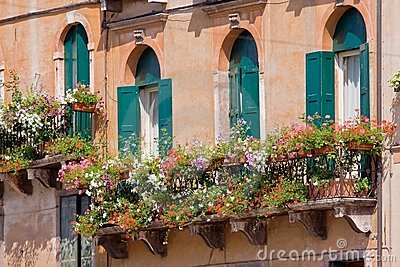 Italian balcony with flowerpots and flowers
