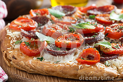 Italian food - pizza with salami and tomatoes, selective focus