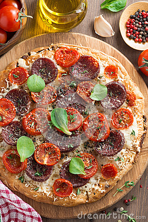 Italian food - pizza with salami and tomatoes, top view