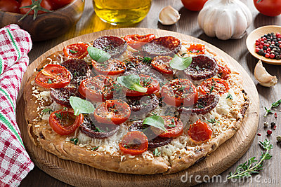 Italian food - pizza with salami and tomatoes on wooden board