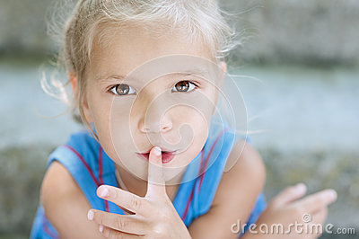 Ittle girl puts her finger to mouth