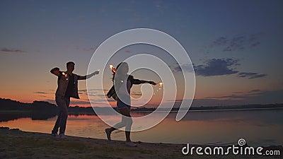 Jóvenes amantes hombres y mujeres corren alegremente a lo largo de la playa con una caliente putrefacción en sus manos en cámar almacen de metraje de vídeo