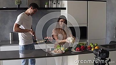 Jóvenes atractivos bloggers de pareja vestidos informales filmando video-food blog sobre su estilo de vida diario, cocinando a fu metrajes
