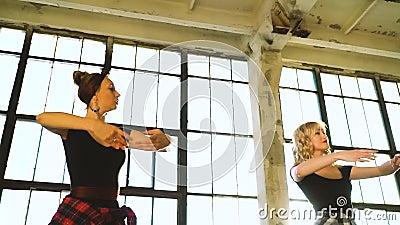 Jóvenes bailarinas practicando movimientos de ballet en estudio de loft almacen de metraje de vídeo