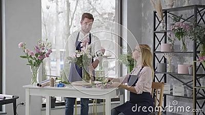 Jóvenes especialistas, colegas mujeres y hombres bello ramo de flores frescas aromáticas en floristería con almacen de metraje de vídeo