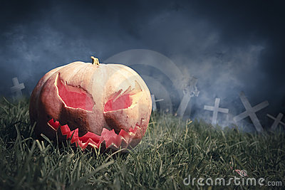 Jack-o-lantern in a graveyard at night