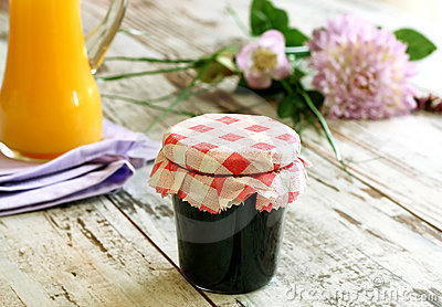 Jam in glass, juice and flowers on wooden