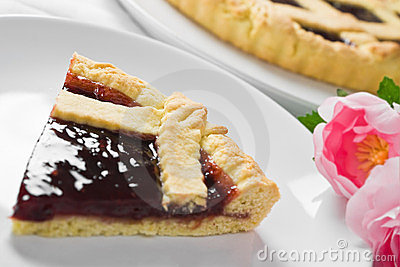 Jam tart slice in white dish.
