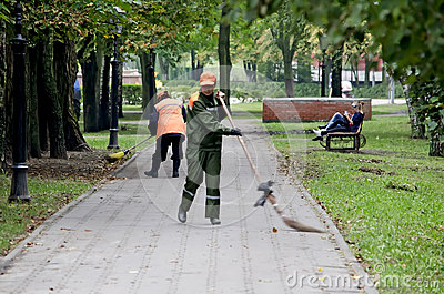 Janitors sweep the sidewalks in the park Editorial Stock Image