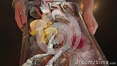 Jantar gourmet: ostras frescas, deliciosas, de alta qualidade, num tabuleiro com gelo, molho e limão filme