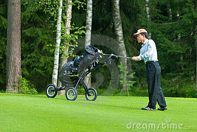 Japaneese golfer finishes his swing Editorial Stock Image