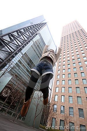 Japanese girl jumping in front of skyscrapers