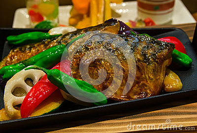 Japanese style grilled saba fish with chilis and vegetables.
