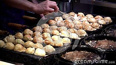 Japanse verkoper bereidt een Takoyaki voor op warme paneten in Osaka, Japan stock videobeelden