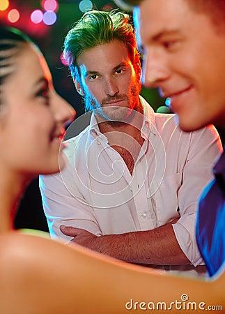 Jealous man looking at dancing couple