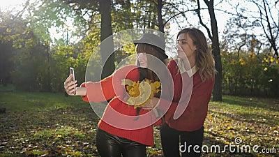 Jesienny sezon, piękne uśmiechnięte młode kobiety przyjaciółki biorące selfie na komórce z bukietem żółtych liści w zdjęcie wideo