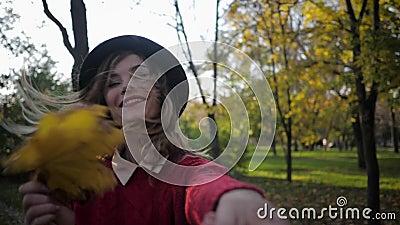 Jesienny sezon, szczęśliwa uśmiechnięta dziewczyna w tym wesołym uśmiechu i trzyma żółte liście w rękach w pięknym parku zbiory wideo