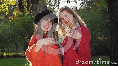 Jesienny sezon, zabawne przyjaciółki śmieją się i wzywają do zabawy żółtymi liśćmi w słońcu w ciepły dzień w parku zbiory wideo