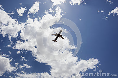 Jet Airliner under broken clouds upon approach