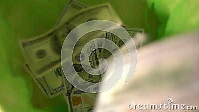 Jetant l'argent, les dollars tombent dans le panier vert de poubelle, absence des finances, gaspillant l'argent clips vidéos