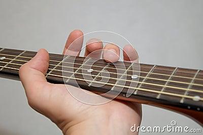 Jeu de la guitare : contact de doigt de flageolet sur la chaîne de caractères