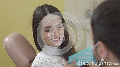 Jeune belle femme dans la chaise dentaire Après la procédure elle regarde dans le miroir Le concept d'un sourire sain banque de vidéos