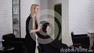 Jeune, belle femme regardant le miroir après une coupe de cheveux terminée Coiffeur brun long après banque de vidéos