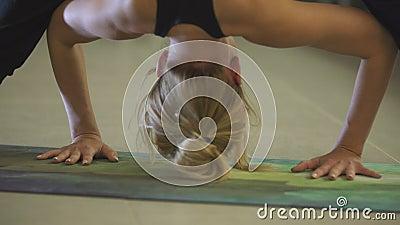 Jeune belle fille caucasienne sportive exerçant des positions de yoga, asana indoors banque de vidéos