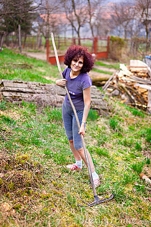 Jeune dame avec le râteau spring cleaning le jardin