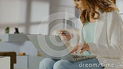 Jeune dame vérifiant l'équilibre sur le compte bancaire utilisant l'ordinateur portable, carte banque de vidéos
