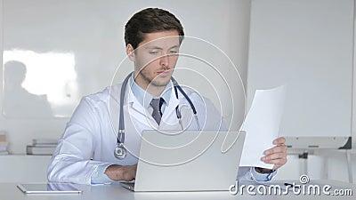 Jeune docteur Working On Laptop et documents médicaux clips vidéos