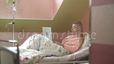 Jeune femme à l'aide de l'ordinateur portable ayant la causerie visuelle sur le lit d'hôpital banque de vidéos