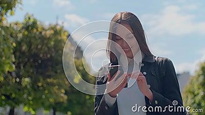 Jeune femme attirante aux rues ensoleill?es de ville et causerie avec des amis, fille joyeuse de hippie ? l'aide du t?l?phone por banque de vidéos