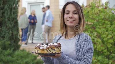Jeune femme attirante avec un gâteau souriant et regardant la caméra. Compagnie de gens qui parlent sur la véranda banque de vidéos