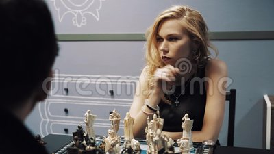 Jeune femme attirante jouant des échecs avec l'homme dans les verres et les promenades loin banque de vidéos