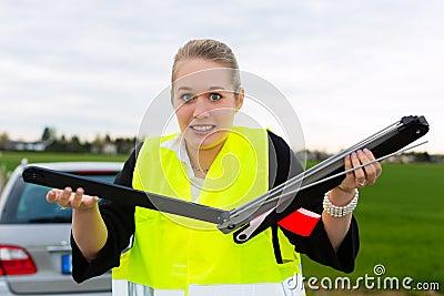 Jeune femme avec la triangle d avertissement sur la rue