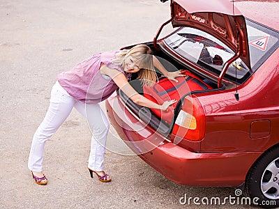 Jeune femme avec une valise rouge dans le véhicule