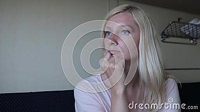Jeune femme blonde voyageant en train, femme attentive assise dans un train, rêvant et relaxant clips vidéos