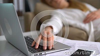 Jeune femme d'affaires fatiguée dormant sur le divan dans le bureau avec l'ordinateur portable Plan rapproché de sa main sur le c banque de vidéos