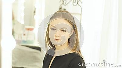 Jeune femme de portrait avec la bride sur des cheveux pendant le maquillage dans le vestiaire Faites face au miroir avant modèle  banque de vidéos