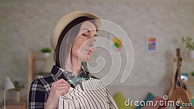 Jeune femme de portrait avec une cicatrice de brûlure sur son visage essayant sur des vêtements devant le miroir clips vidéos