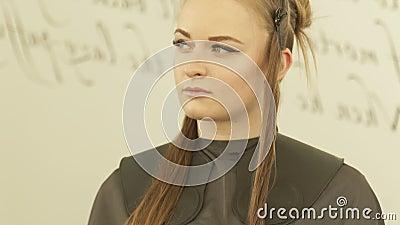 Jeune femme de visage avec la bride sur des cheveux pendant haircutting dans la fin de salon de coiffure  Modèle femelle de cheve banque de vidéos