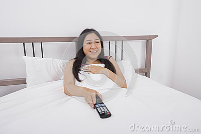 Jeune femme heureuse regardant la TV dans le lit