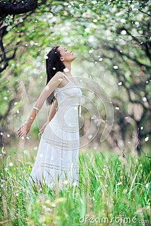 Jeune femme insousiant dans la robe blanche
