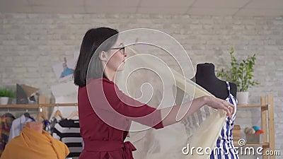 Jeune femme mignonne vêtement de créateur de mode dans des lunettes travaillant avec le tissu lent clips vidéos