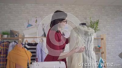 Jeune femme mignonne vêtement de créateur de mode dans des lunettes travaillant avec des tissus clips vidéos