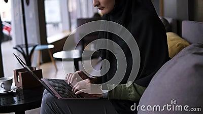 Jeune femme musulmane concentr?e travaillant sur l'ordinateur portable moderne en caf? Femme attirante dans le hijab tenant l'ord banque de vidéos