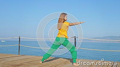 Jeune femme qui s'étire à la jetée en bois sur fond de mer ou d'océan banque de vidéos
