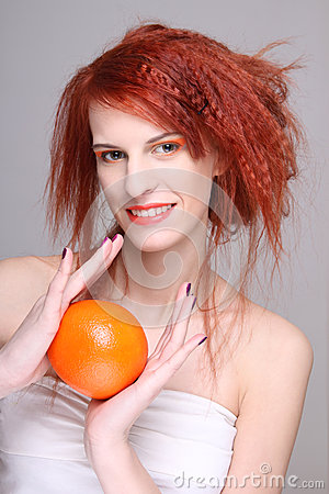 Jeune femme redhaired avec l orange dans des ses mains